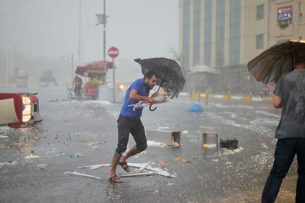 A man holds an umbrella during a heavy downpour of hail at Taksim in Istanbul on July 27, 2017.