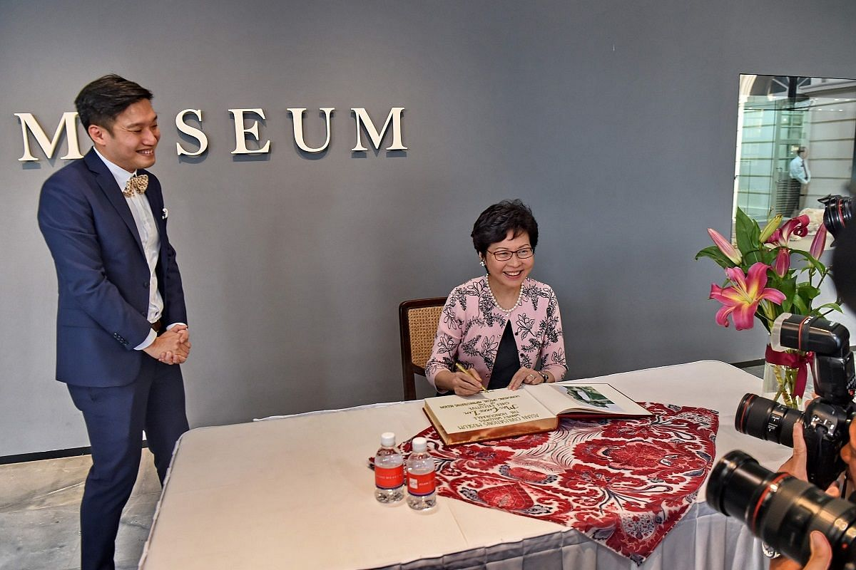 Mrs Carrie Lam signing a guest book during her tour of the Tang Shipwreck Gallery at the Asian Civilisations Museum on Aug 2.