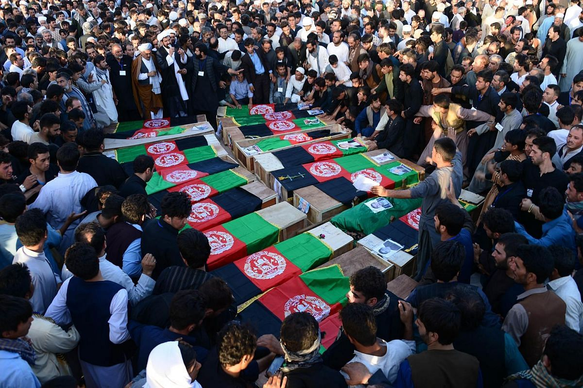 Afghans gather around coffins of victims as they shout anti-ISIS slogans following a mosque attack that killed 33 people in Herat, Afghanistan.