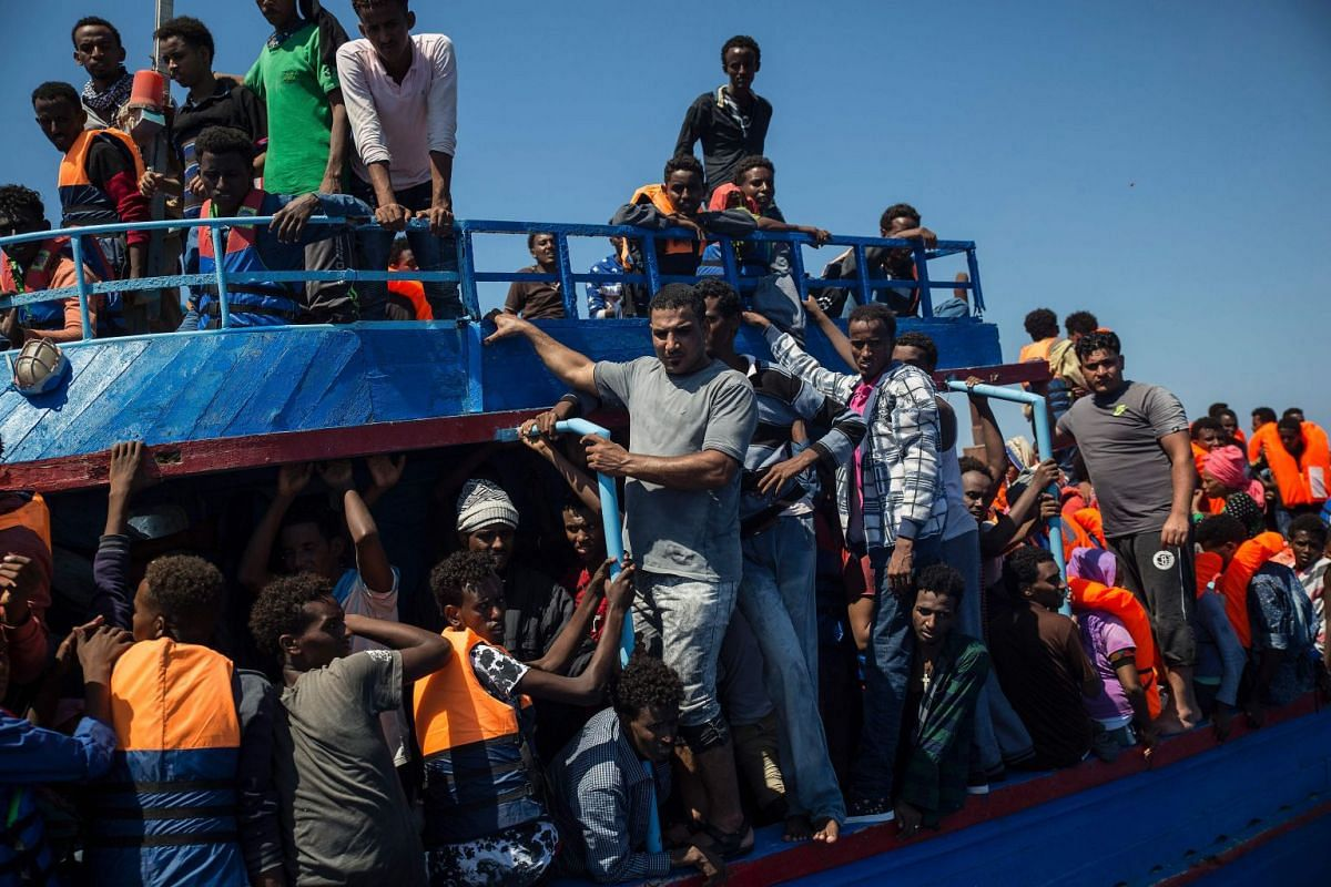 """Migrants wait to be rescued by the Aquarius rescue ship run by non-governmental organisations (NGO) """"SOS Mediterranee"""" and """"Medecins Sans Frontieres"""" (Doctors Without Borders) in the Mediterranean Sea, 30 nautic miles from the Libyan coast."""