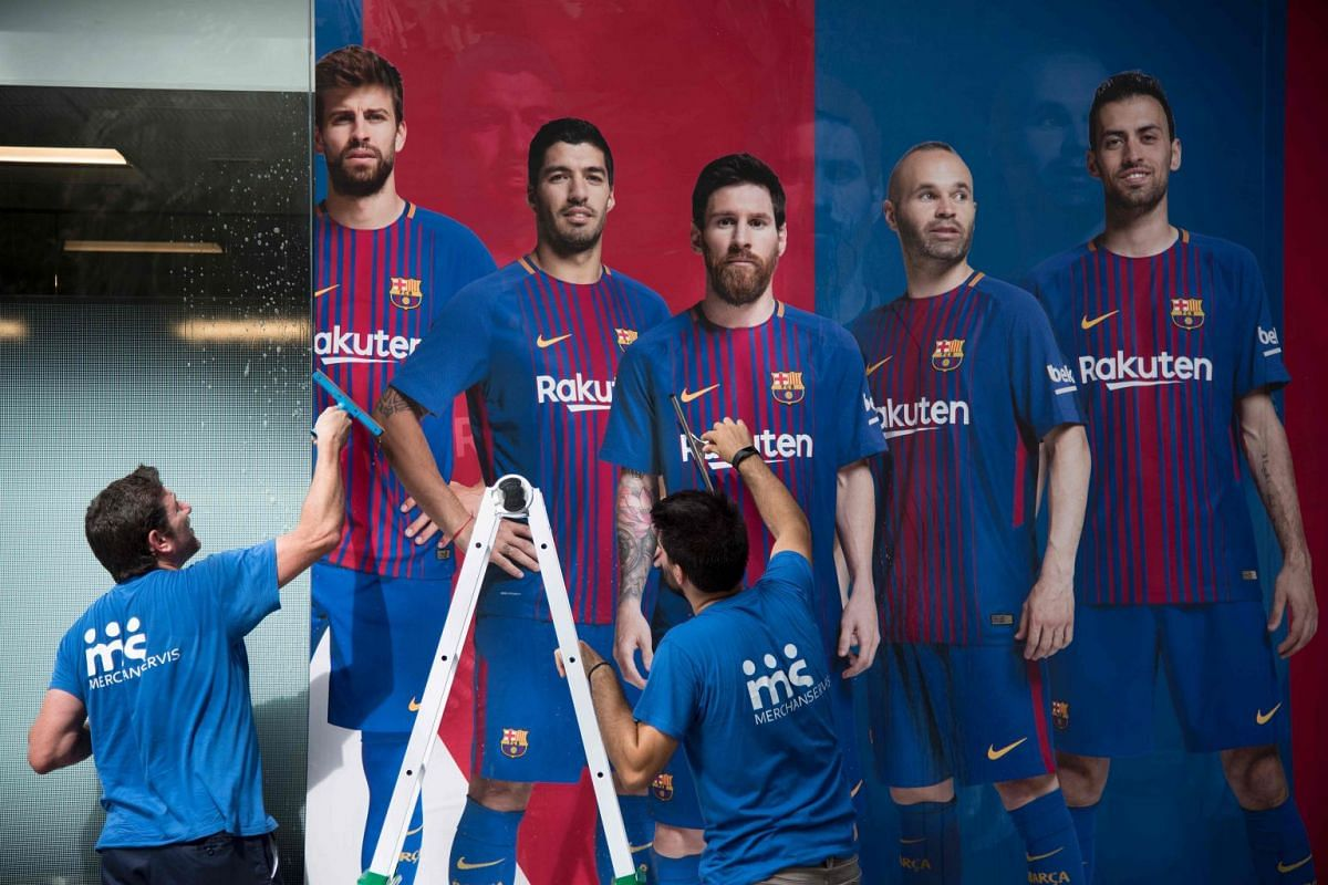 Two men put up a new poster featuring Barcelona FC footballers in Barcelona.