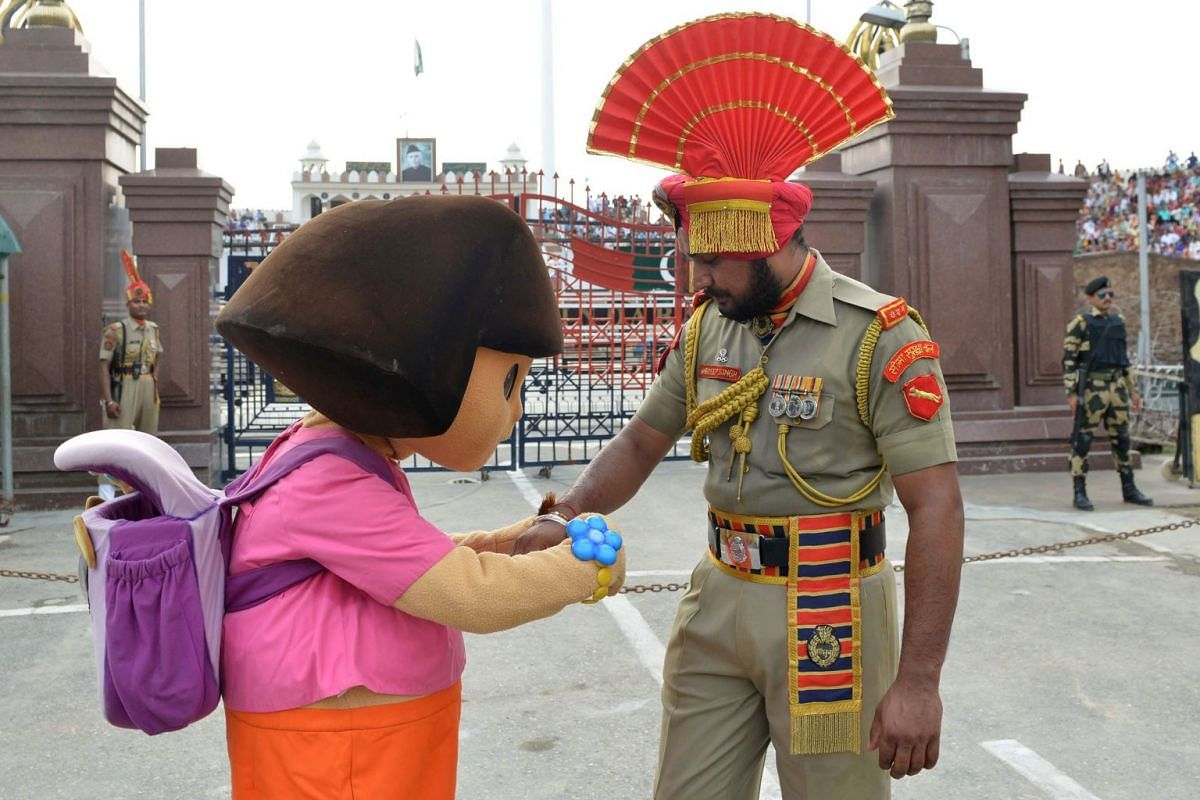 Cartoon character Dora the Explorer ties a sacred thread known as 'Rakhi' onto the wrist of an Indian Border Security Force personnel during celebrations before the Raksha Bandhan festival at the India-Pakistan Wagah Border.