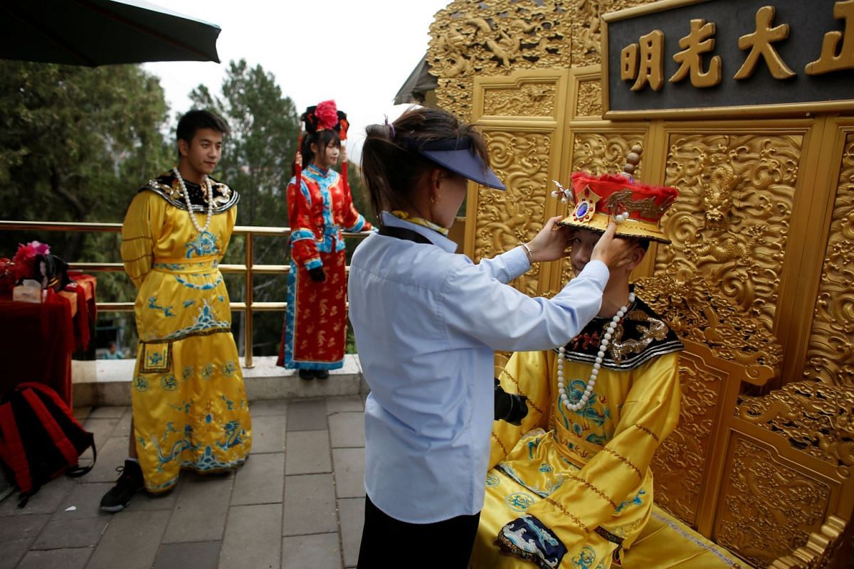 A staff member adjusts a tourist's costume before he has pictures taken in Jingshan Park, one of the major tourist spots in Beijing, China.