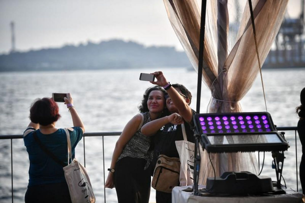 Visitors take selfies by the ocean at the Marina Bay Cruise Centre.