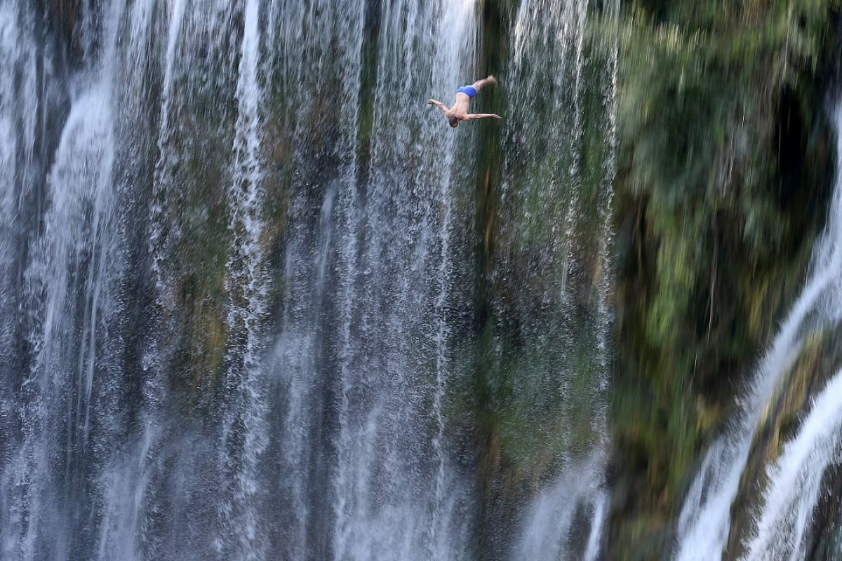 A competitor in the annual international waterfall jumping competition held on Aug 5 in the old town of Jajce, Bosnia and Herzegovina.