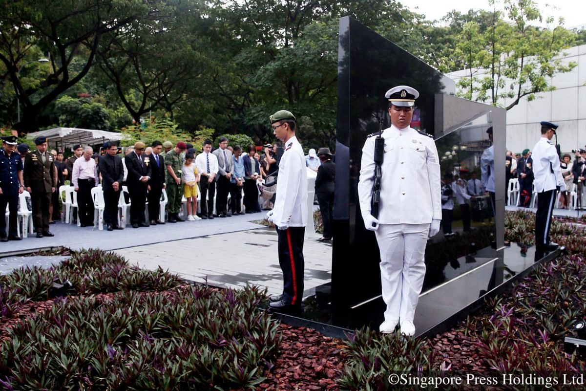 2016: Attendees observing a moment of silence at a memorial to honour the volunteers and soldiers who defended Singapore during Konfrontasi, the period of hostilities with Indonesia in the 1960s.