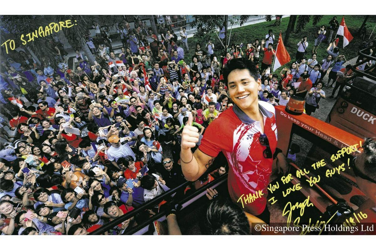 2016: Poster of Singapore's first Olympic champion Joseph Schooling posing with thousands of fans who showed up at his victory parade. He won the gold medal in the 100m butterfly in the 2016 Rio Games, beating his own swimming idol.