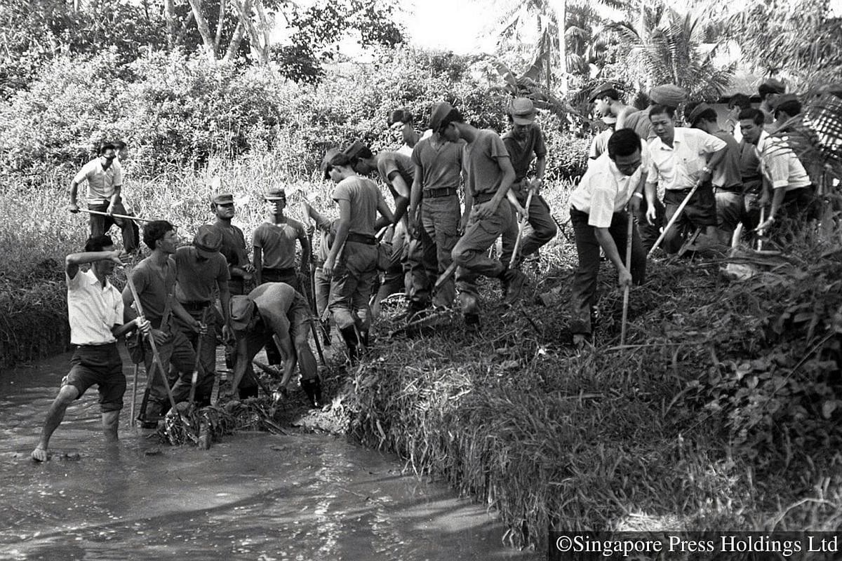 "1973: Working towards a common goal - villagers and national servicemen desilting Sungei Pang Sua in Bukit Panjang to mark the start of ""Keep Our Water Clean"" campaign. They spent hours shovelling mud and weeds from the river, which carries rain wate"
