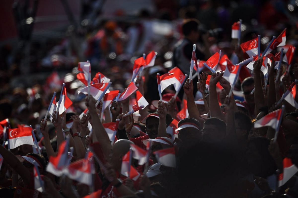 People in the crowd waving flags during the National Day Parade on Aug 9, 2017.