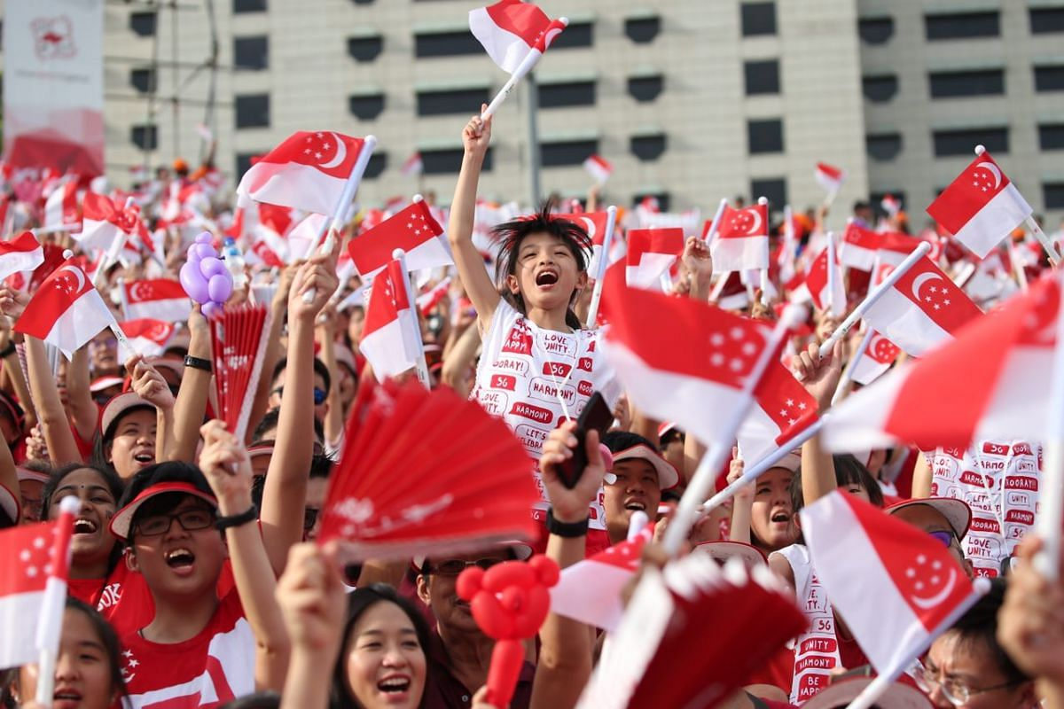 Members of the audience waving flags during the National Day Parade on Aug 9, 2017.