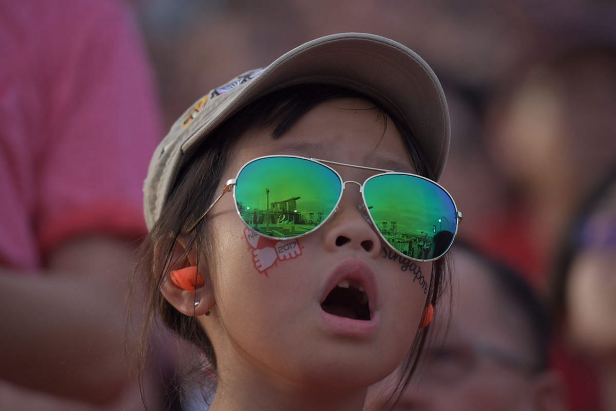 Marina Bay Sands is reflected in the sunglasses of a young child at the Floating Platform, during the National Day Parade, on Aug 9, 2017.