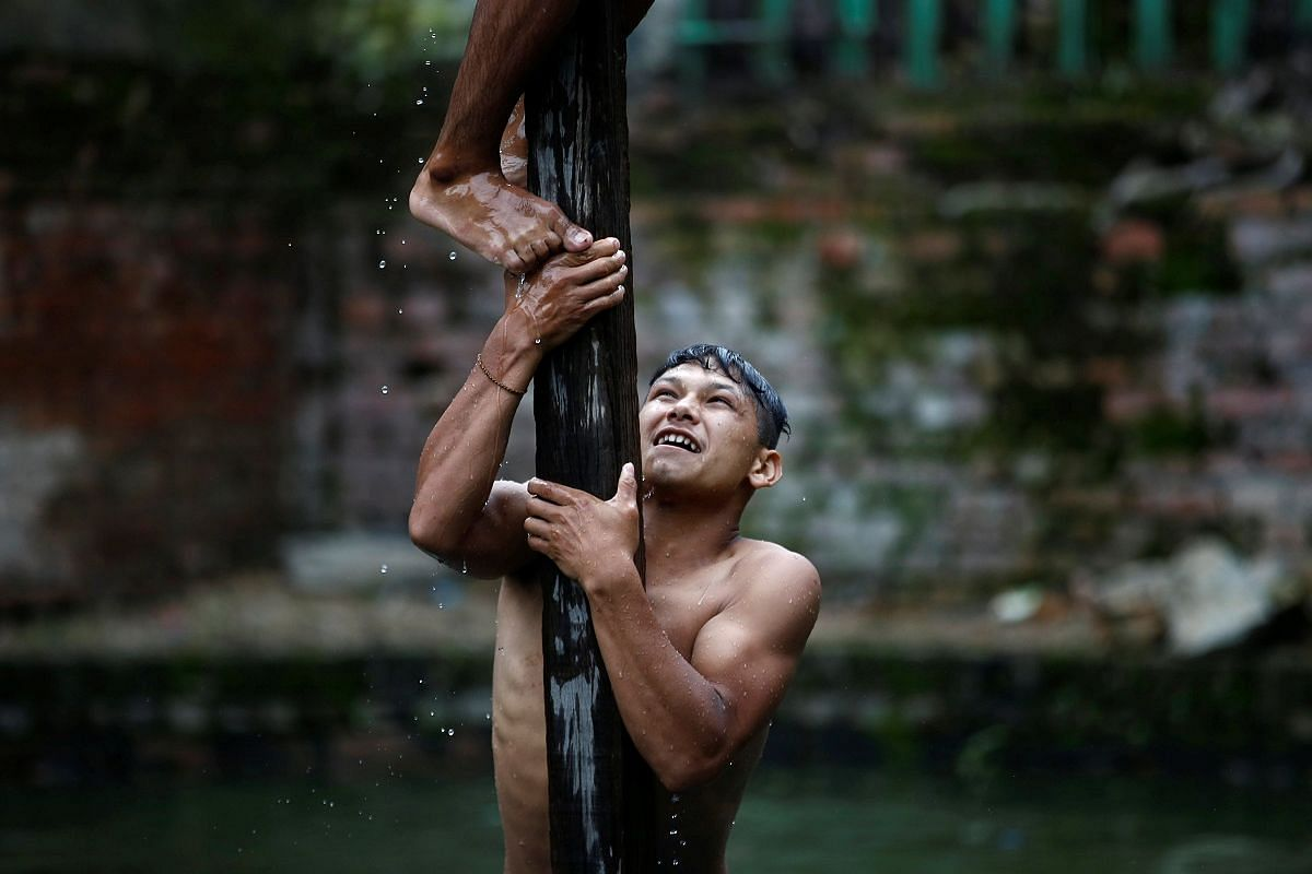 A devotee helps his friend climb a wooden pole in the Deopokhari festival in Khokana, Nepal, on Aug 9. During the annual festival, a live goat is thrown into a pond and the team of devotees that retrieves the animal first wins.