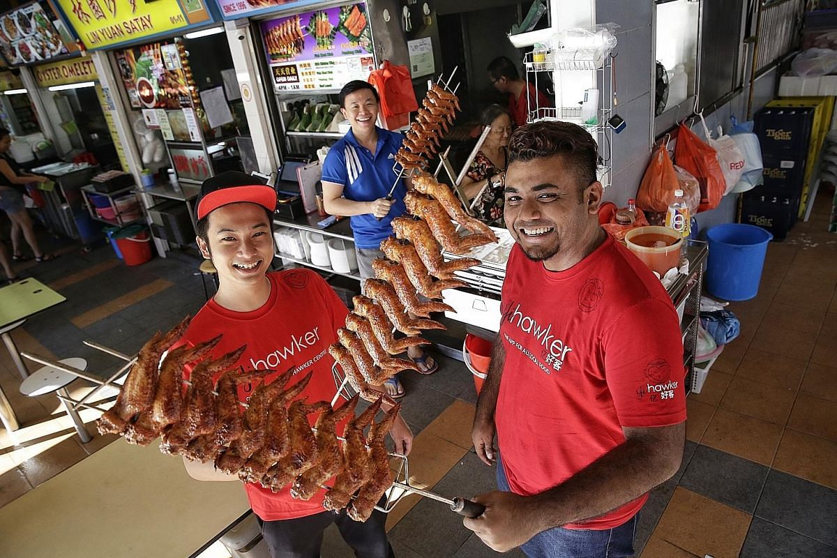 Yihawker founder Jonathan Tan (far left), 27, and co-founder Muhd Nur Azhar Mohd Maideen, 25, with Mr Larry Ng (centre), 33, who runs Sin Bedok North BBQ Chicken Wing.