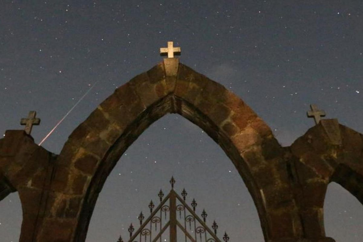 A meteor from the Perseid meteor shower burns up in the atmosphere behind a Catholic church near the village of Rubezhevichi, in Minsk, Belarus.