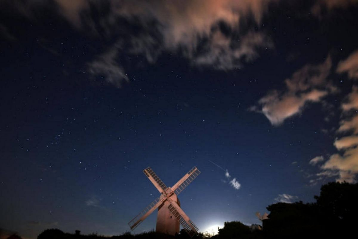 A meteor streaks past stars in the night sky above the Jill Windmill, during the Perseid meteor shower in Brighton, southern Britain.