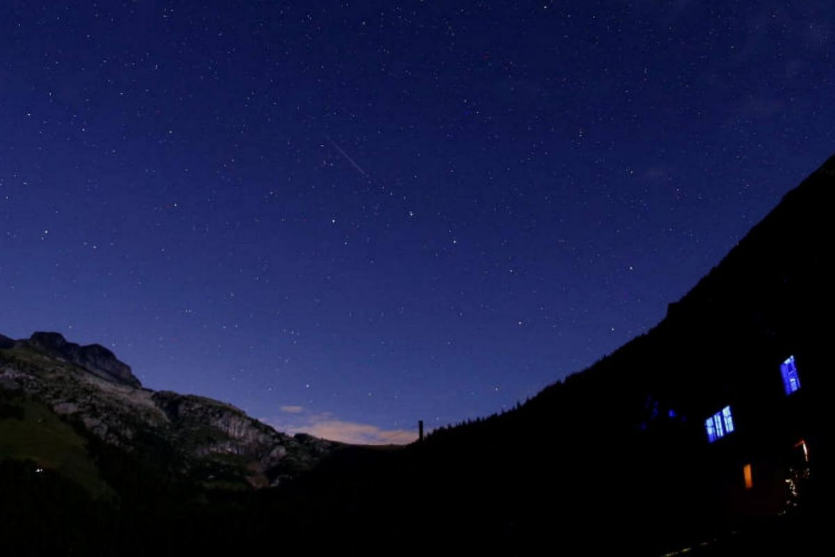 A meteor streaks past stars in the night sky during the annual Perseid meteor shower in Le Sepey, Switzerland.