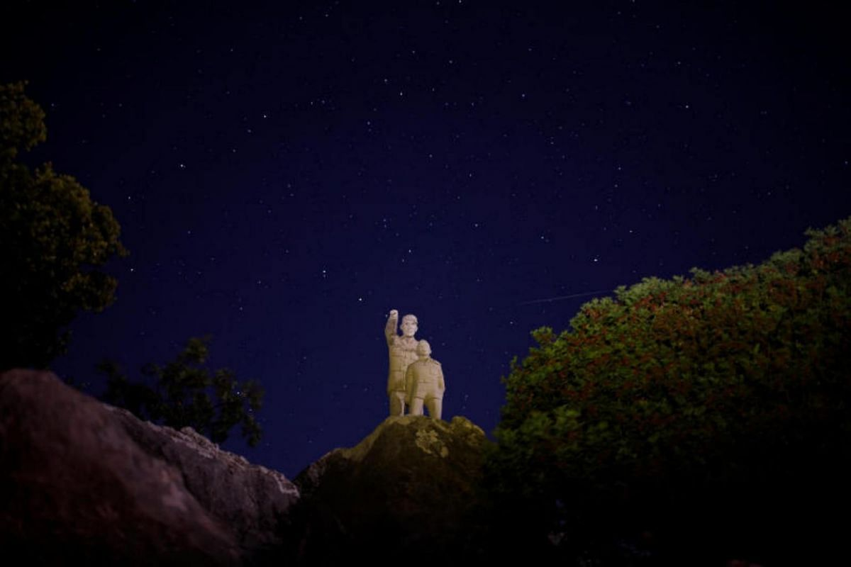 A meteor streaks past stars in the night sky over the statues of a man and a boy, during the annual Perseid meteor shower at the Sierra de las Nieves nature park and biosphere reserve near Malaga, Spain.