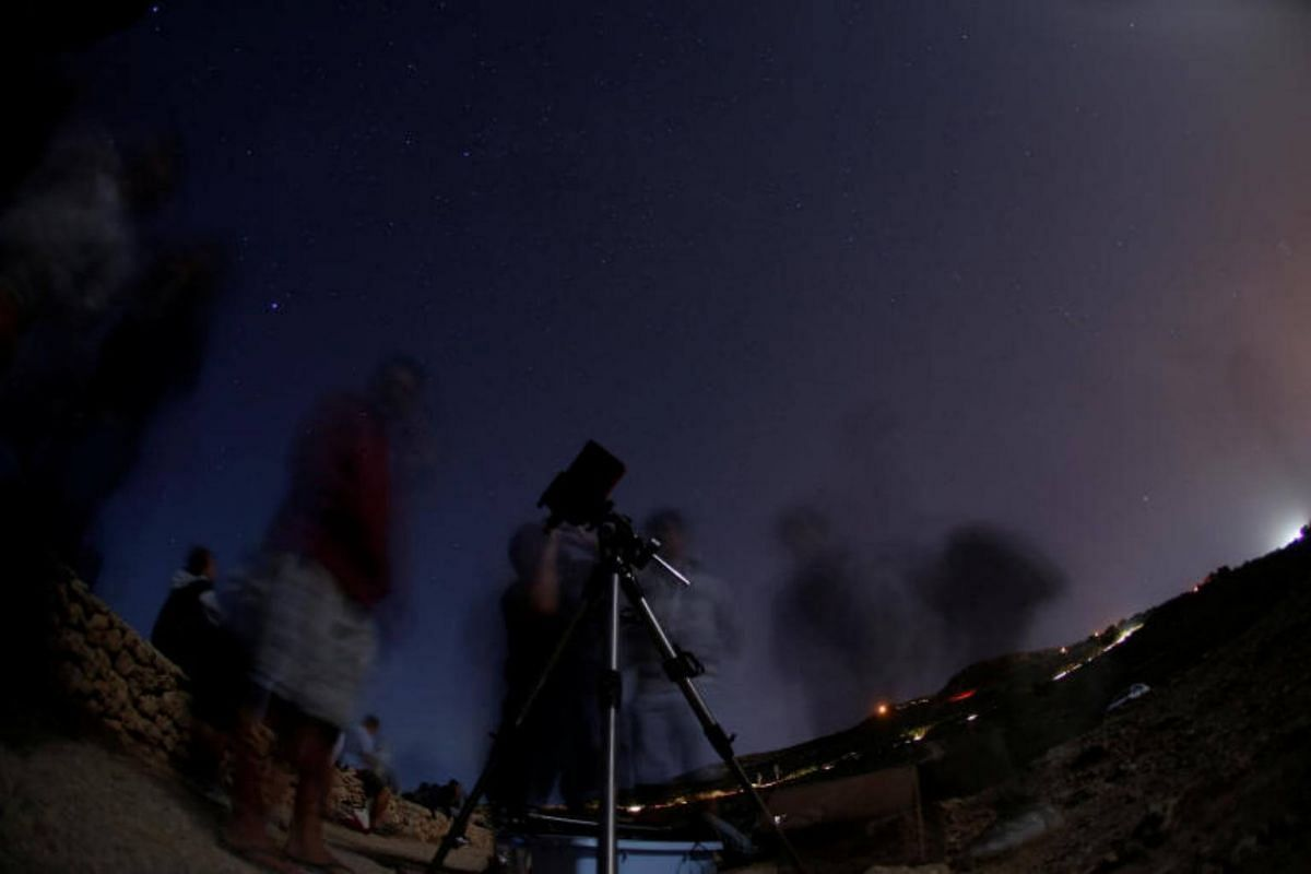 A man looks at the moon through a telescope during the Perseid meteor shower at Migra l-Ferha, outside the town of Rabat, Malta.