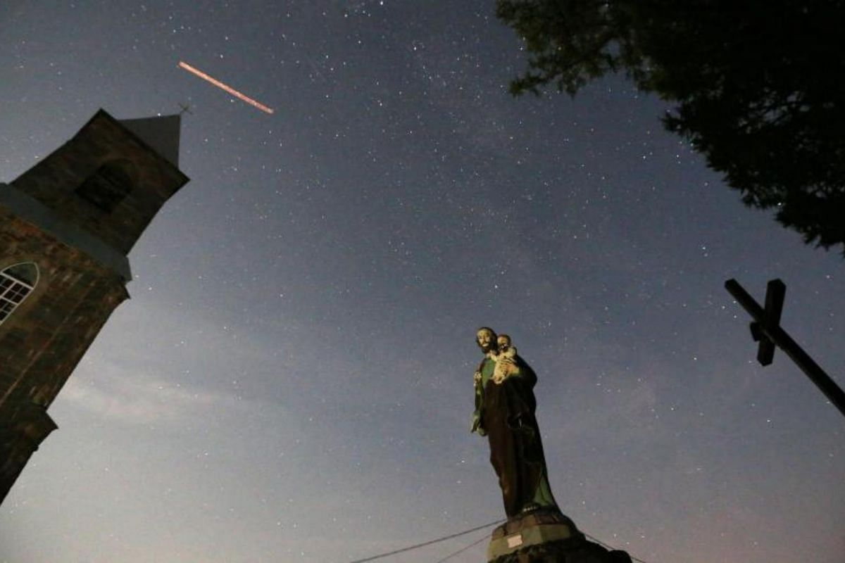 A Catholic statue, cross and a church are seen during the Perseid meteor shower near the village of Rubezhevichi, in Minsk, Belarus.