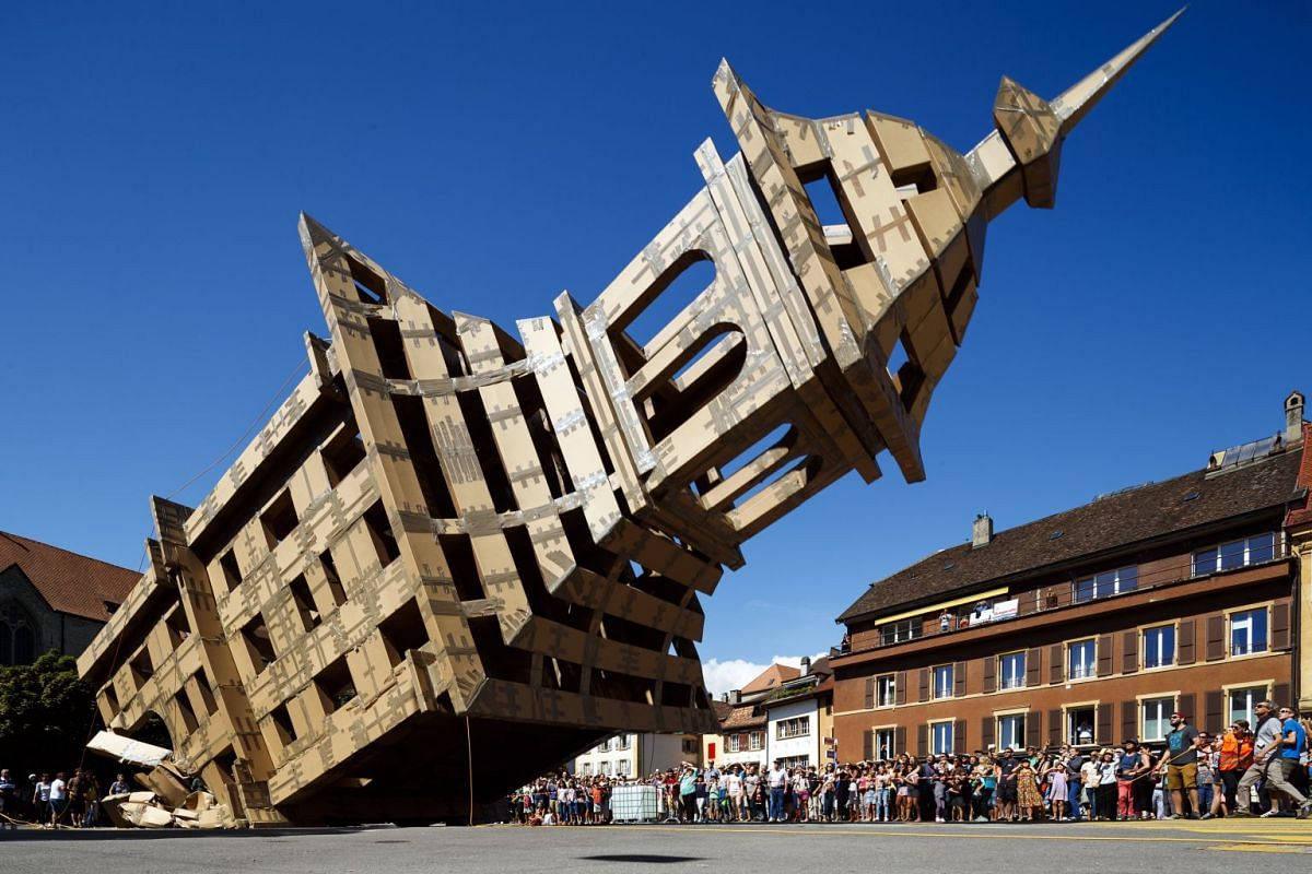 """A cardboard tower with a height of 20 meters and a weight over a tone is brought down during the street festival """"Les Jeux du castrum"""" in Yverdon-les-Bains, Switzerland, August 13, 2017. PHOTO: EPA"""
