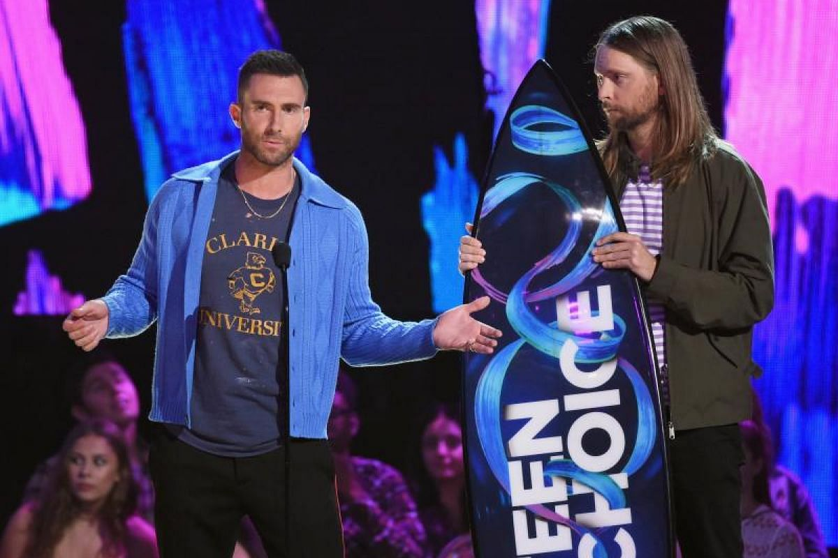 Adam Levine (left) and James Valentine of American pop-rock band Maroon 5 accept the Decade Award onstage during the Teen Choice Awards 2017.