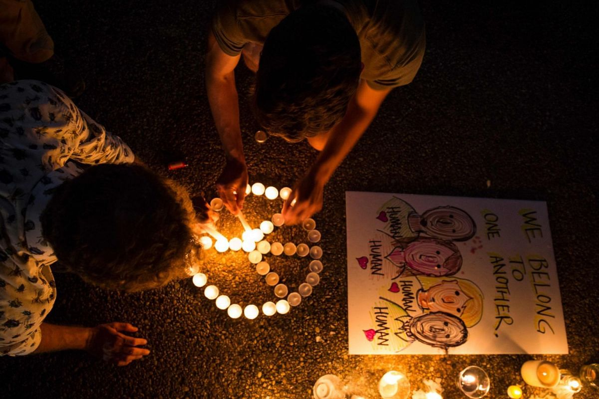 People arranging lighted candles in the form of a peace sign in front of the White House.