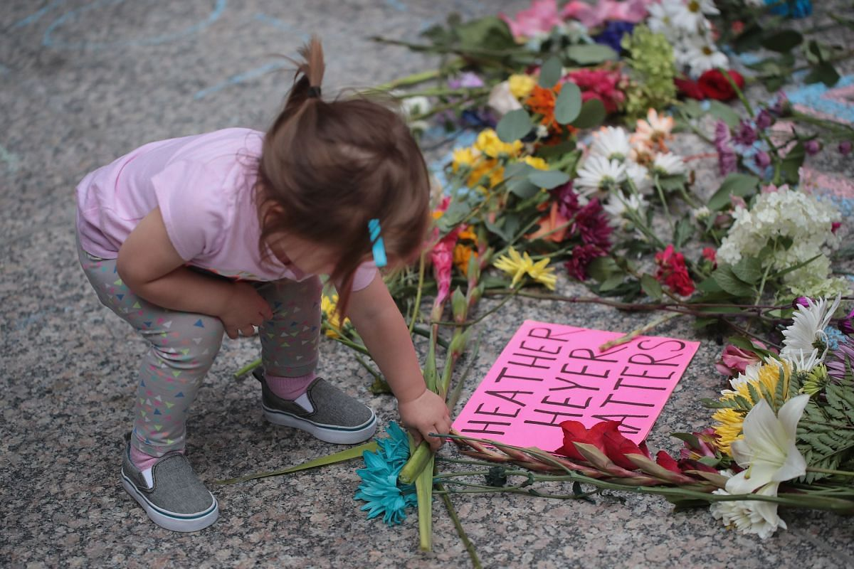 A young girl putting flowers on a memorial to Ms Heather Heyer in Chicago, Illinois.