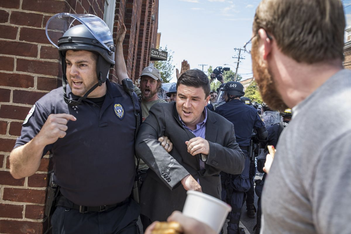 Mr Jason Kessler, who organised the Unite the Right rally, being escorted away by police in Charlottesville on Sunday after he was punched by a protester at a news conference he had planned in front of the City Hall.