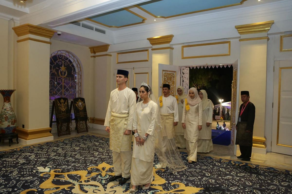 "Princess Tunku Aminah wears an elegant white ""Baju Kurung"" (traditional female Malay attire) with western-styled trail, while Dennis looks charming in a similarly matching white ""Baju Melayu"" (traditional Malay men's attire) with ""samping"