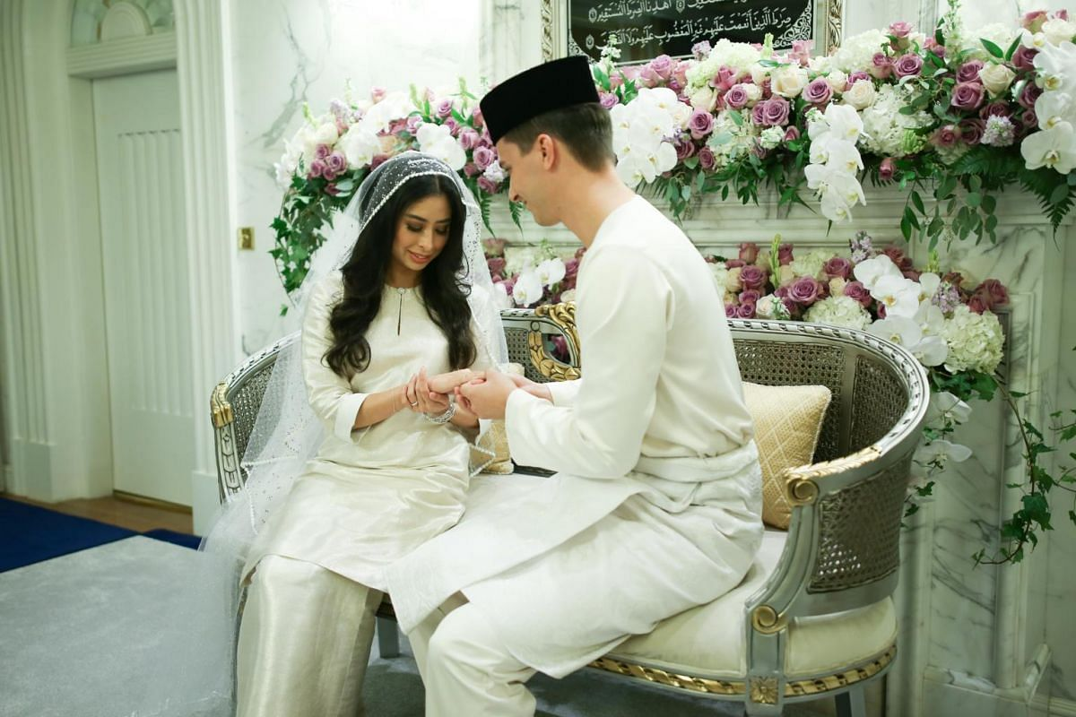 The groom Dennis Muhammad placing the wedding ring on the finger of his bride Tunku Tun Aminah after their marriage solemnisation ceremony in Johor Bahru today.