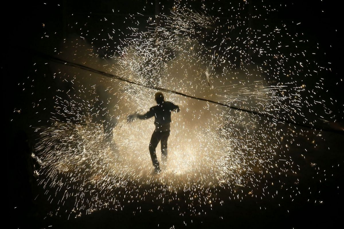 A man performing during the Wheelbarrow War spectacle at the festivity of the Nit de l'Alba (Night of the Alborada) in honour of the Assumption of Mary, in Elche, eastern Spain, on Aug 13.