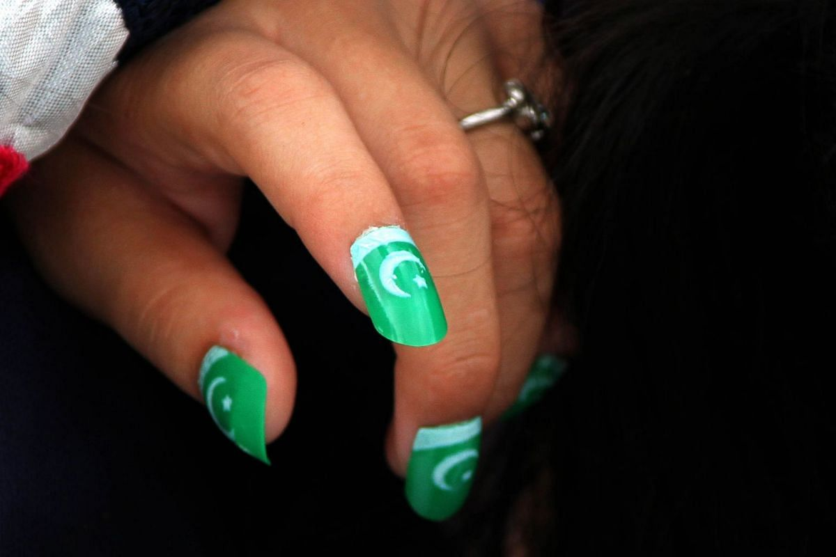 A patriot to her fingertips - a girl in Karachi wearing artificial nails in the colours of the national flag.