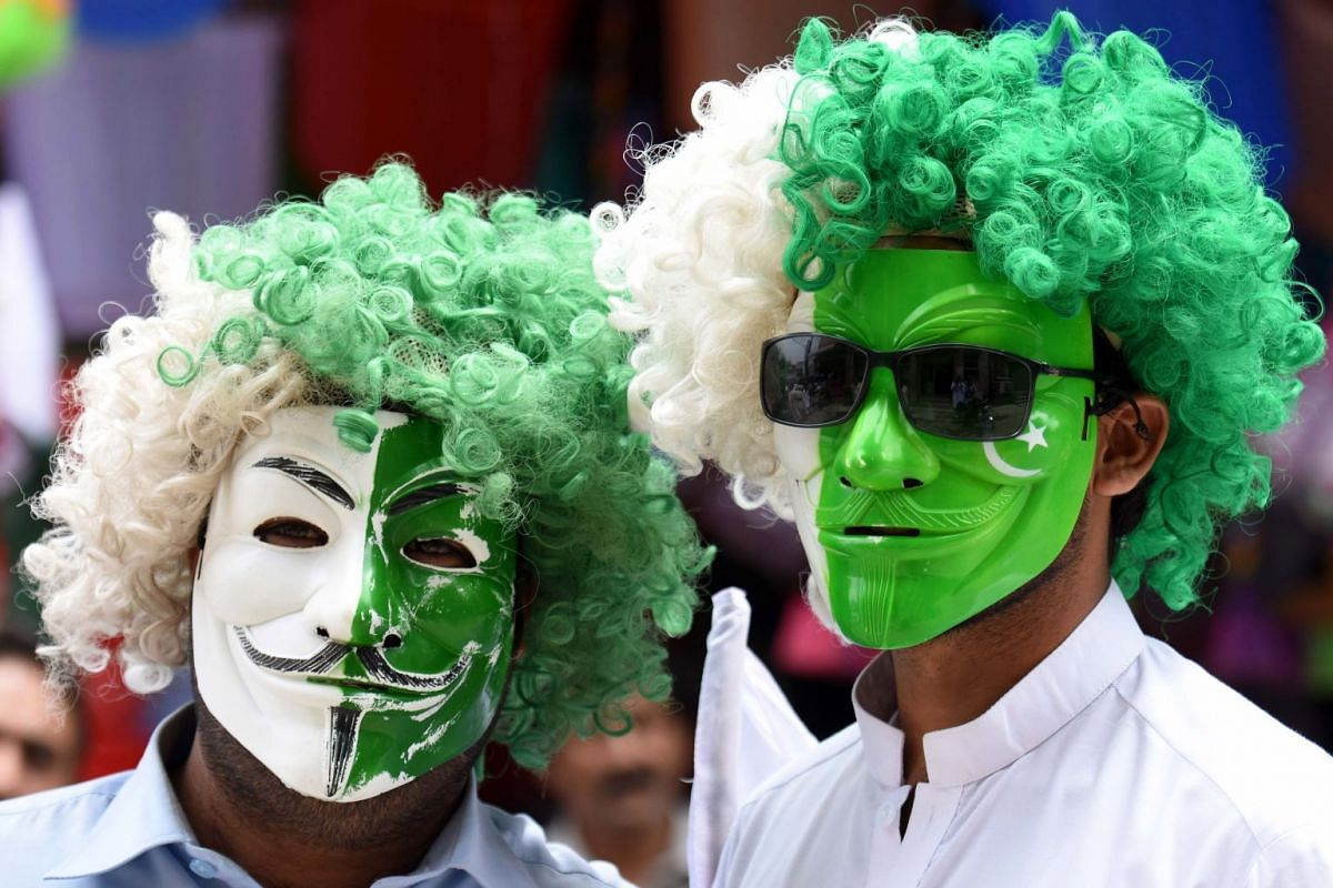 Men in Peshawar get into the spirit of things with colourful masks and wigs.