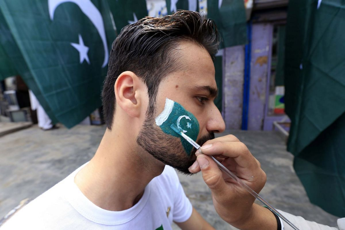 A man getting his face painted with the national flag in Peshawar.