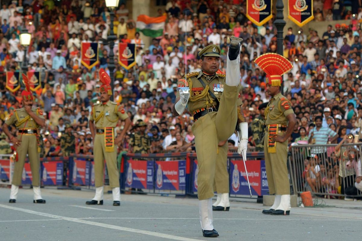 Indian Border Security Force personnel in an elaborate military display at the Wagah Border Post. Freedom from British colonial rule in 1947 was accompanied by the partition of the sub-continent into India and Pakistan - an event that continues to pl