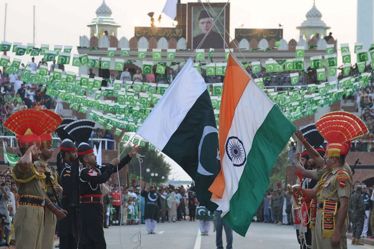 Pakistani Rangers (in black) and Indian Border Security Force personnel lowering their respective nations' flags at the beating of the retreat ceremony at the Wagah Border Post, the only functioning land-border crossing with India.
