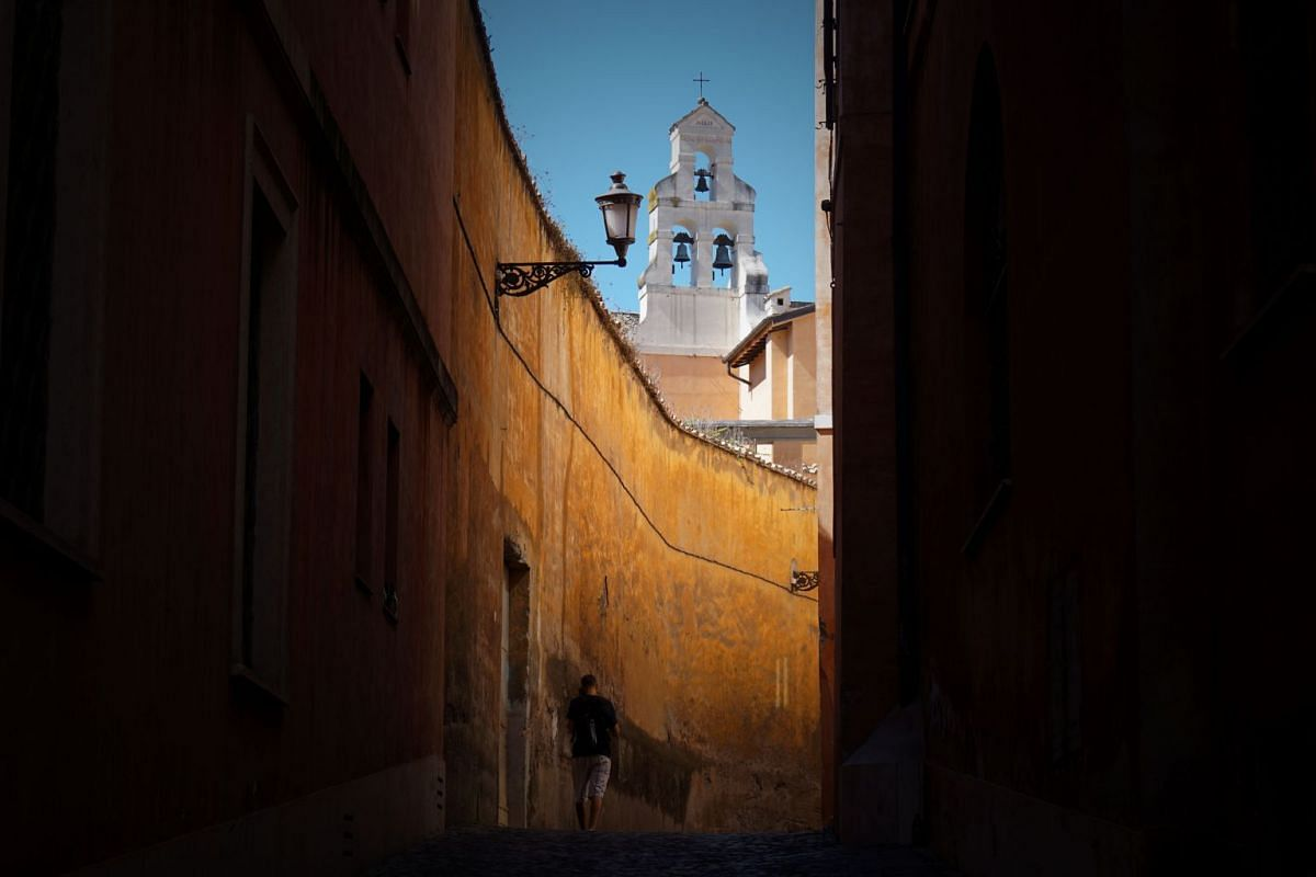 A man walking in a narrow street in Rome on Aug 14.