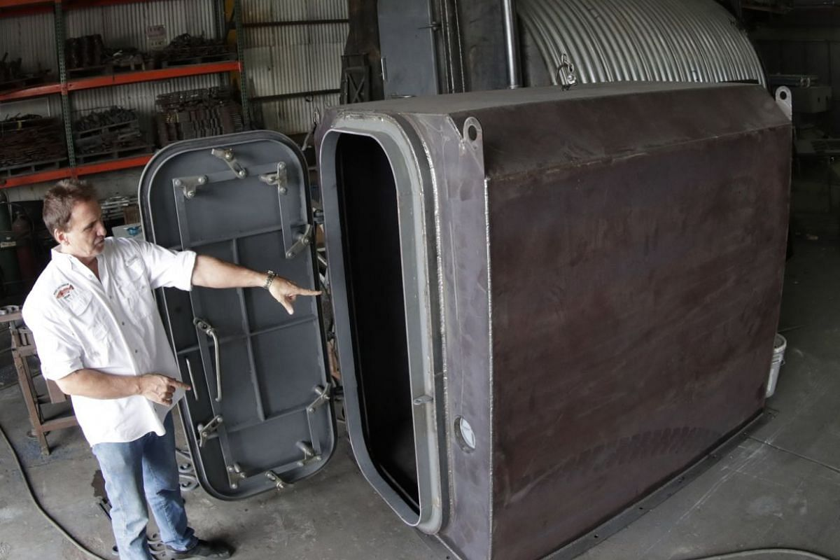 Mr Hubbard showing the FallNado bomb shelter, which sits above ground and is designed to fit inside a home garage.