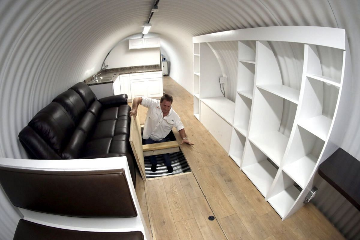Mr Hubbard showing the storage space beneath the floor of a deluxe model.