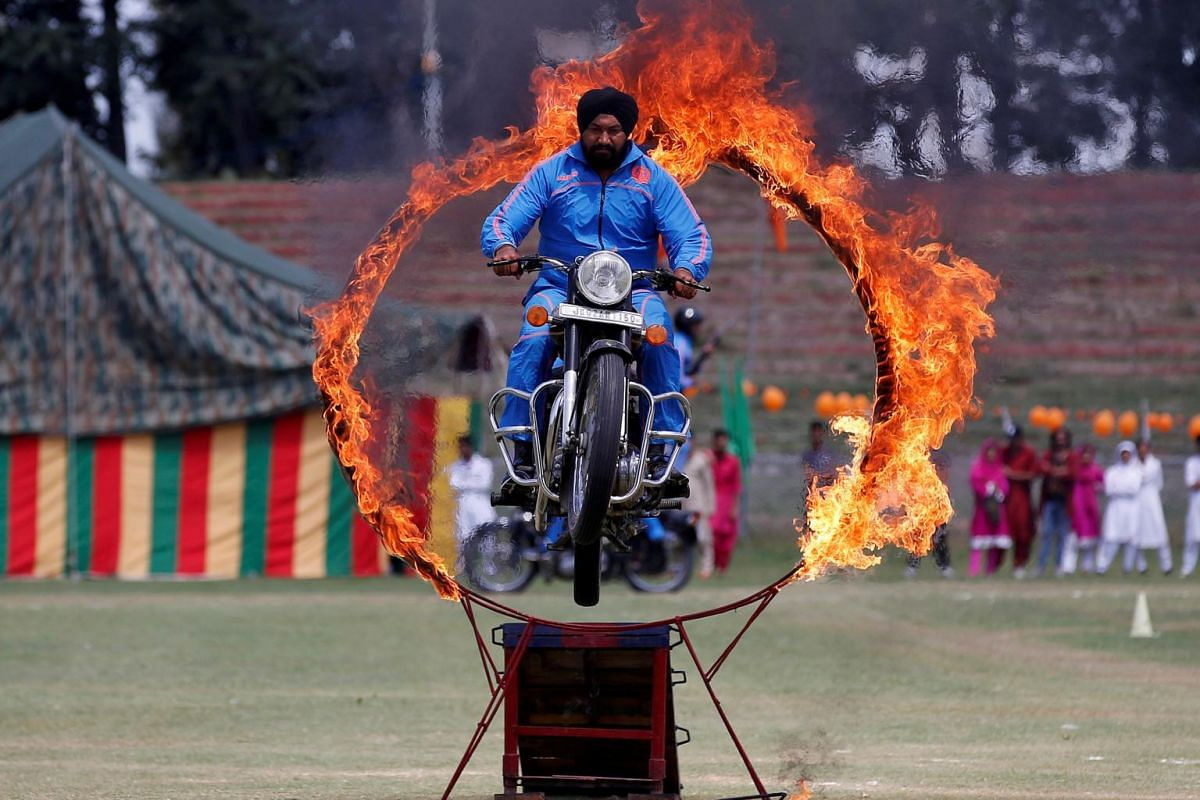 A policeman performs a stunt on a motorbike through a ring of fire during India's Independence Day celebrations in Srinagar, on Aug 15, 2017.
