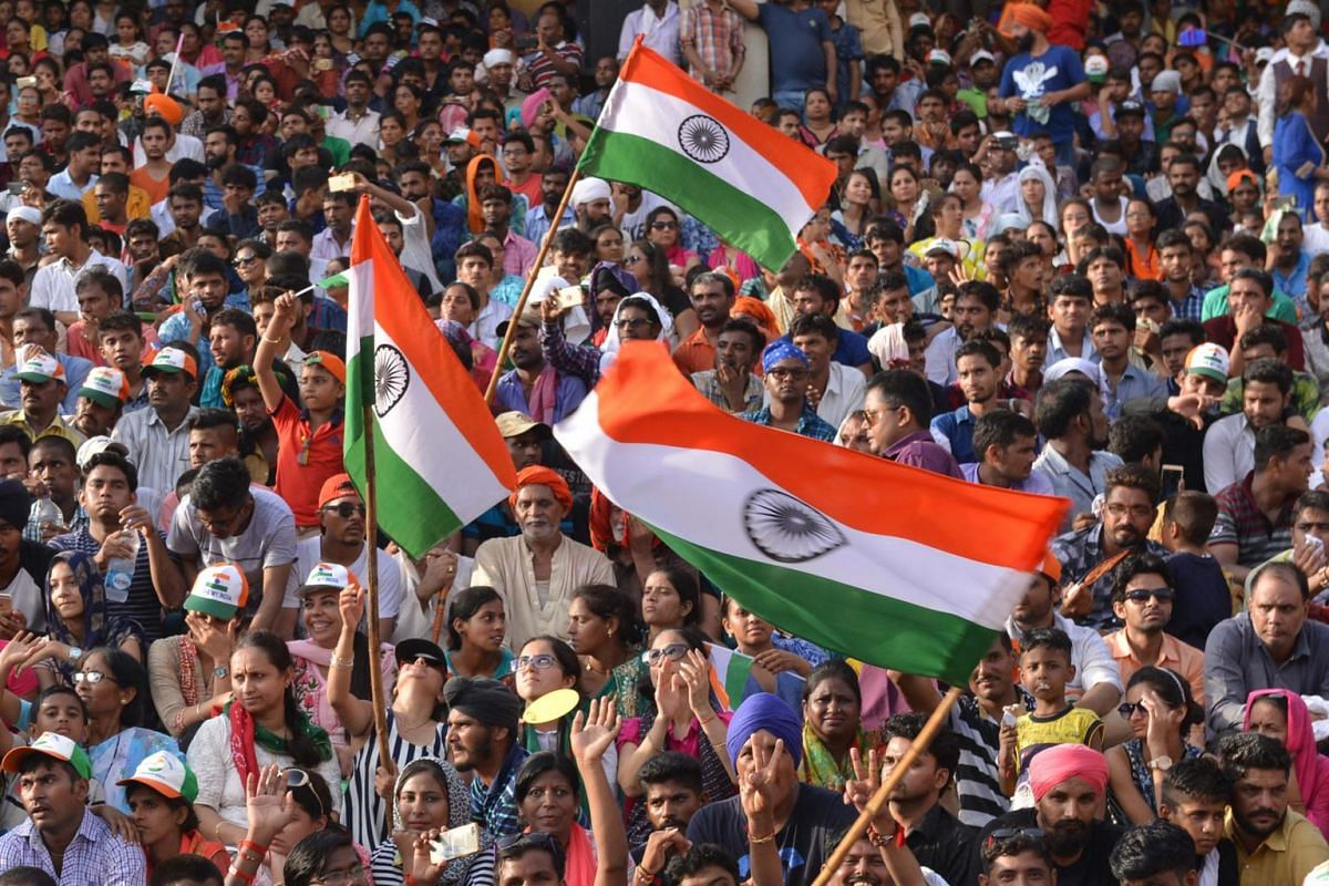 Indian tourists wave Indian flag during the daily beating of the retreat ceremony at the India-Pakistan Wagah Border Post, some 35kms west of Amritsar, on Aug 15, 2017.