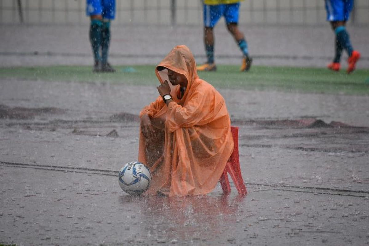 A ball boy sits in the rain during the SEA Games football match between Myanmar and Singapore at the Selayang Stadium in Kuala Lumpur on Monday (Aug 14).