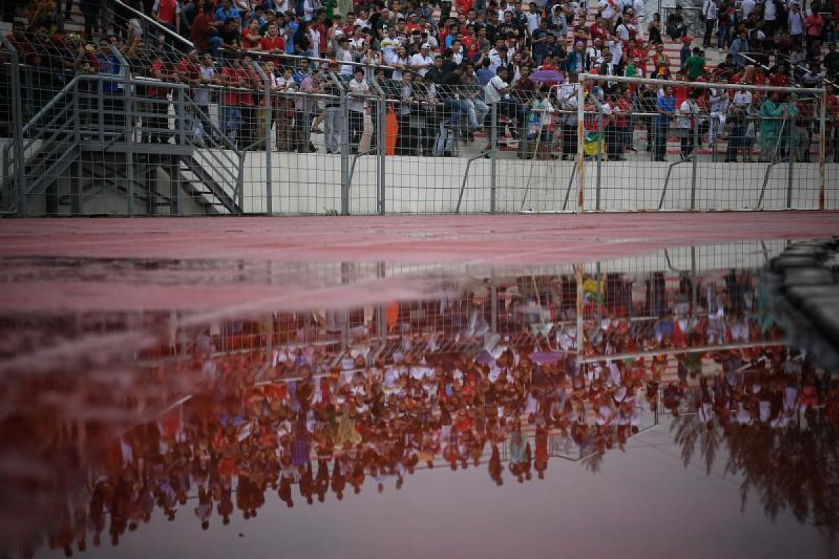 Myanmar football fans are reflected in a puddle of water during the SEA Games football match between Myanmar and Singapore at the Selayang Stadium in Kuala Lumpur on Monday (Aug 14).
