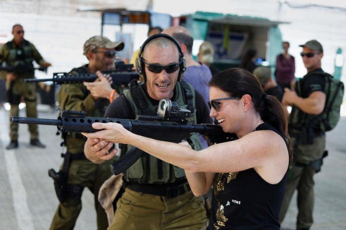 Foreign tourists are taught how to use a gun as they participate in a two hour anti-terror course at the Caliber 3 shooting range, near the West Bank settlement of Efrat.