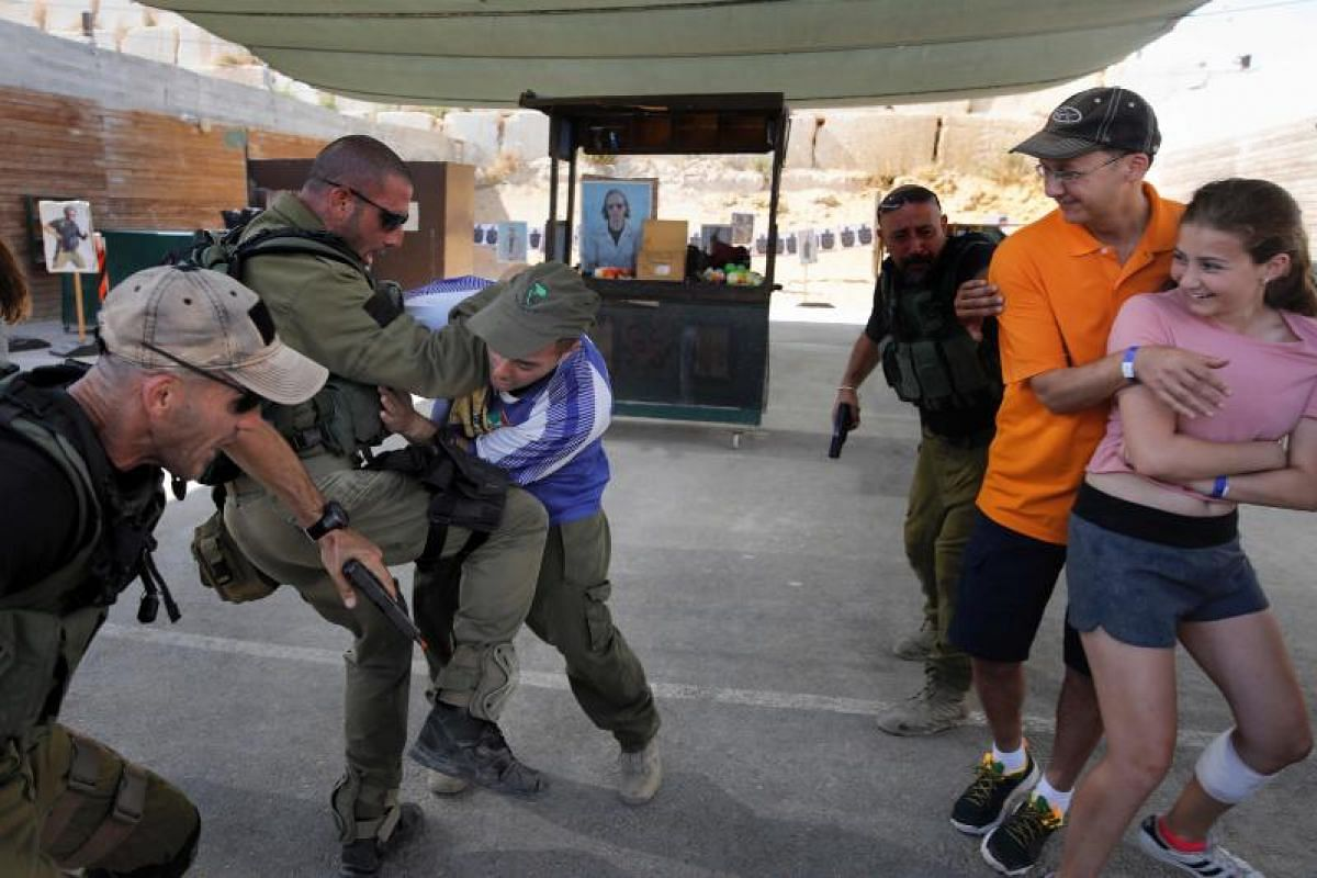 Foreign tourists watch as Israeli instructors neutralize a man during a simulation of a knife attack at a market, as they participate in a two-hour anti-terror course at the Caliber 3 shooting range, near the West Bank settlement of Efrat.