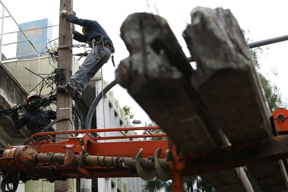 Thai electricity workers climb on the power pole (L) as they cut the poles off before removing from a roadside in Bangkok, Thailand, Aug 16, 2017. The overhead power lines and cables in Bangkok are being moved underground to improve the look of the c
