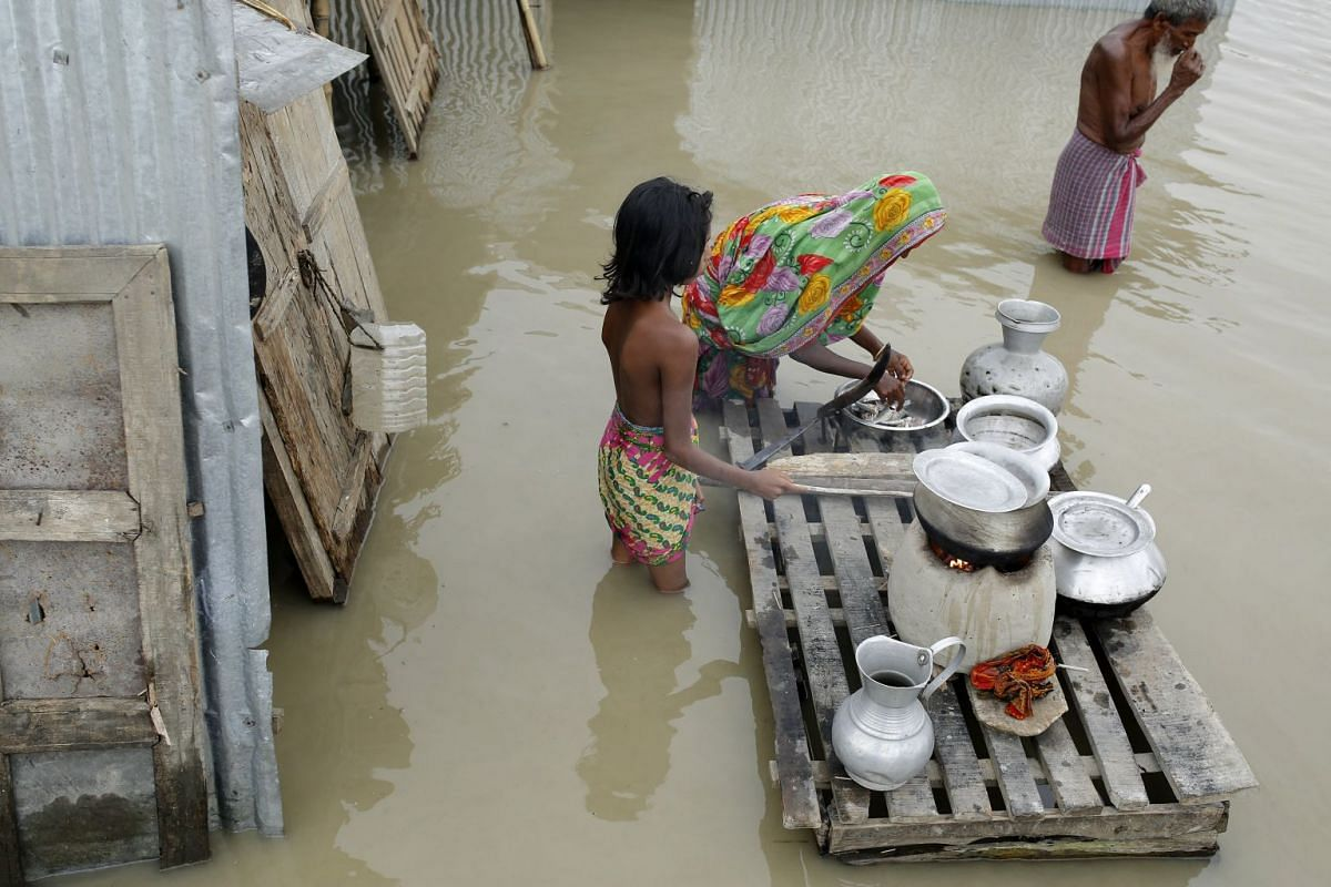 A woman cooks food in front of her flooded house near a river island formed from sedimentation, known as a 'char' at Mainkdir, Sariakandi, Bogra, Bangladesh, Aug 16, 2017. Flood victims are facing severe shortages of drinking water and food. Many flo