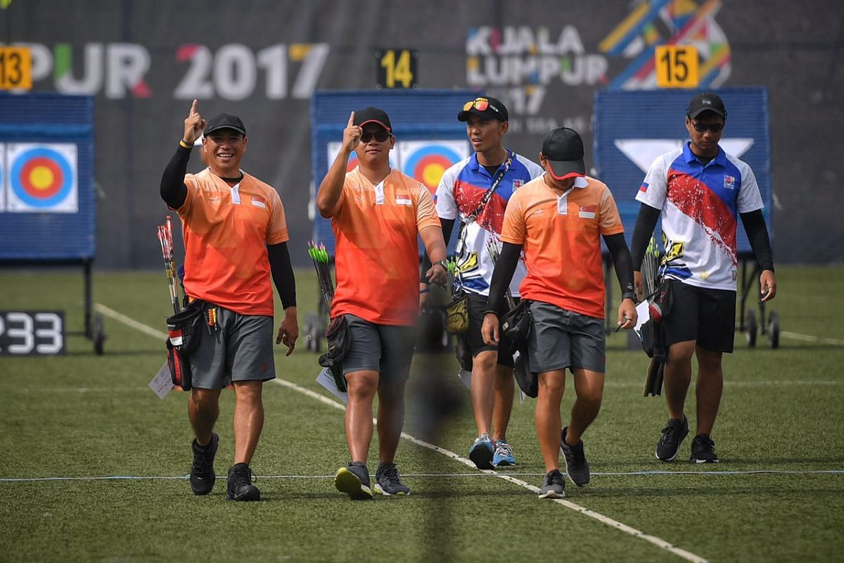 Singaporean archers (from left) Alan Lee, Pang Toh Jin and Ang Han Teng gesture after making the finals of the SEA Games compound men's team event on 17 August, 2017.