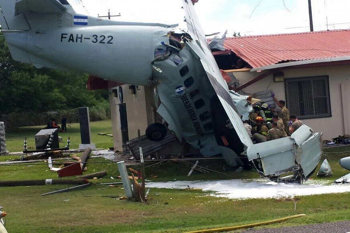 Firefighters and soldiers working to extract from the wreckage the crew membrs of a Honduran Air Force Let-410 twin-engine transport aircraft that crashed on a house at the U.S. military base of Palmerola in Comayagua, 70 km north of Tegucigalpa on A