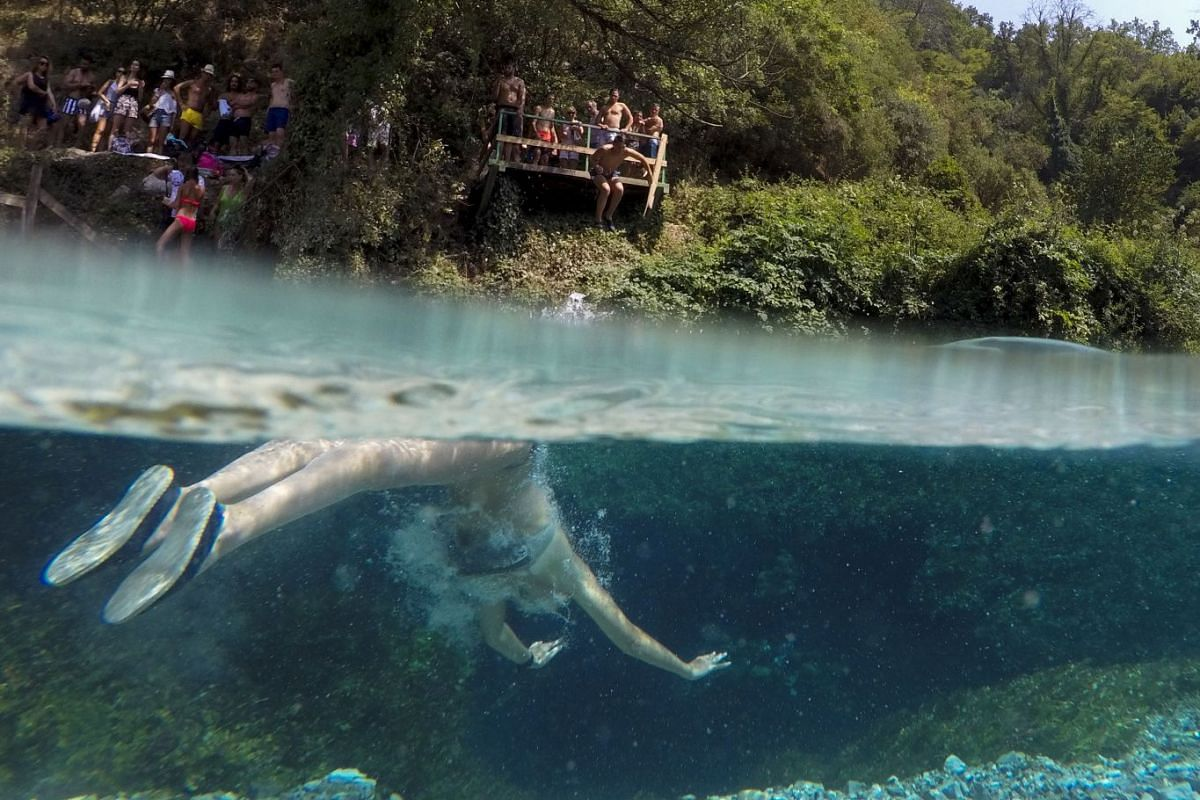A man swims to cool off in the Blue Eye water spring and natural phenomenon occurring near the city of Sarande, on August 16, 2017.
